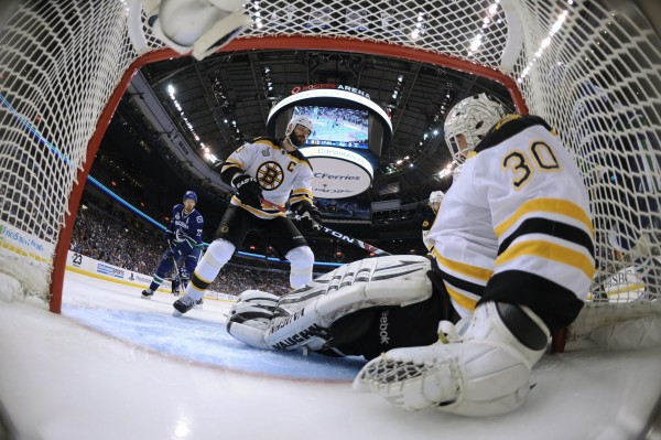 Boston Bruins goalie Tim Thomas (30) covers up the puck as Bruins defenseman Zdeno Chara (33) looks on with Vancouver Canucks' Daniel Sedin (22) during the second period of Game 7 of the NHL hockey Stanley Cup Finals at Rogers Arena, Wednesday, June 15, 2011, in Vancouver, British Columbia.