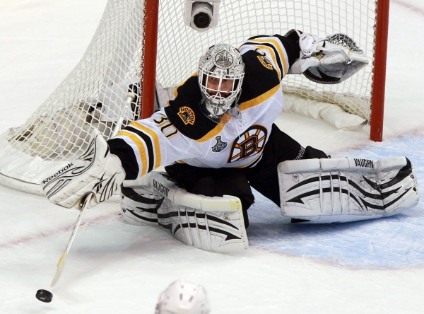 Boston Bruins goalie Tim Thomas turns the puck away against the Vancouver Canucks during the third period of Game 7 of the NHL hockey Stanley Cup Finals on Wednesday, June 15, 2011, in Vancouver, British Columbia.