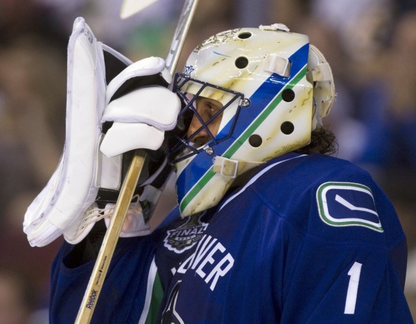 Vancouver Canucks goalie Roberto Luongo adjusts his mask after the third goal by the Boston Bruins, during the second period of Game 7 of the NHL hockey Stanley Cup Finals on Wednesday, June 15, 2011, in Vancouver, British Columbia.