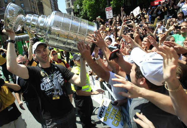 Boston Bruins captain Zdeno Chara carries the Stanley Cup as fans reach to touch the trophy during a rally in celebration of their NHL hockey Stanley Cup playoff victory in Boston., Saturday, June 18, 2011.