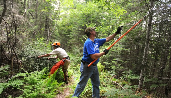 John Bajkowski of Spectra Energy (right) and Roger Chandler of the Inland fisheries and Wildlife work on clearing a trail at the Sunkhaze Meadows National Wildlife Refuge in Milford Wednesday afternoon, June 29, 2011.  They were among the 14 volunteers who worked on the trails to get some much needed clearing done.