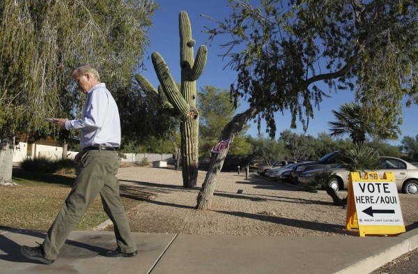 In this Tuesday, Nov. 2, 2010 file photo, a voter arrives at his polling station to deliver his ballot on election day in Phoenix. The Supreme Court on Monday, June 27, 2011 struck down a provision of a campaign financing system in Arizona that gives extra money to publicly funded candidates who face privately funded rivals and independent groups.