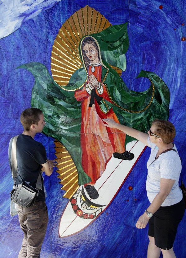In this May 27, 2011 photo, Anthea Beletsis, right, of Encinitas, Calif.,  and Jules Itzkoff, of Cincinatti, Ohio, look at an image of the Virgin of Guadalupe riding a surfboard that hangs under a train bridge in Encinitas, Calif. The unauthorized artwork is drawing a mass following, and even city officials who say she must go say they too have been taken by her.