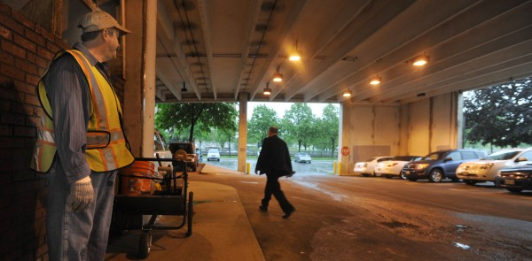 "Bill King (left), a laborer with Bangor Public Works, stopped his downtown trash detail to take cover in Pickering Square Parking garage as Wednesday morning's thunderstorm passed over Bangor. ""When it's severe they don't want me out there,"" said King of the storm and his employer."