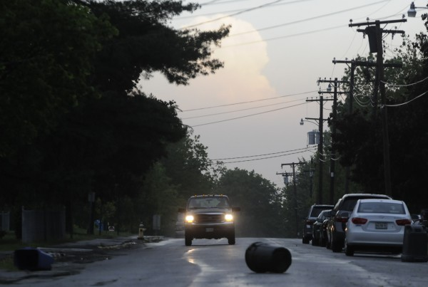A pickup truck gets ready to dodge a trash can blown onto Thirteenth Street during Wednesday morning's thunderstorm.