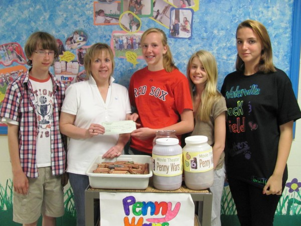 Students at Warsaw Middle School who helped organize a recent &quotPenny Wars&quot effort present thousands of pennies they raised and a matching check from the student council to Lori Glidden, chair of the theater's ongoing fundraising campaign on Friday, June 17, 2011. Shown from left are Jacob Burbine, seventh grade; Glidden; Student Council President Cassie Miller, eighth grade; Mia Fox, seventh grade; and Rachel Lanzikos, eighth grade.
