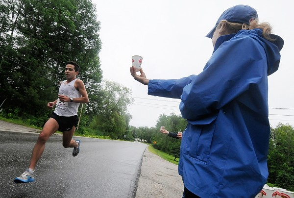 Eventual winner Louie Luchini (left) of Ellsworth passed on hydration as Sub 5 Track Club vice president Samantha  Matoush (right) of Bangor worked with other volunteers at two-mile water station during the 36th Tour Du Lac 10 miler in Bucksport on Saturday morning, June 25, 2011. Luchini, who also won last year, ran the course in 50:20, breaking the Gerry Clapper's 25-year-old record by 26 seconds.