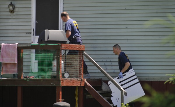 Maine State Police Evidence Response Team members carry boxes Friday morning to collect evidence from the Amity home where two men and a young boy were stabbed to death last year.