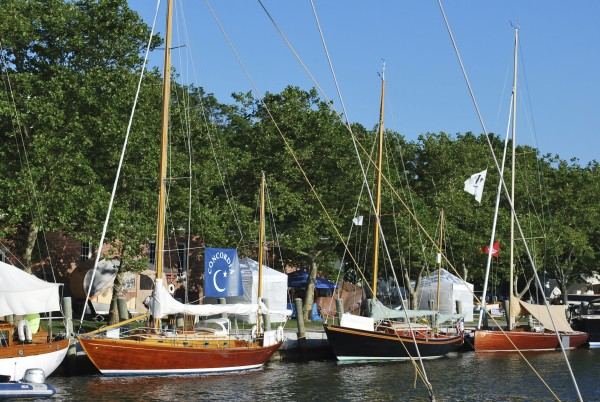 A flotilla of wooden boats is lined up along the shore at a previous WoodenBoat Show. The show is sponsored by WoodenBoat Publications in Brooklin and will run from June 24-26 at Mystic Seaport in Mystic, Ct.