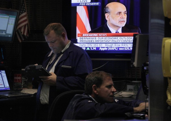 Federal Reserve Chairman Ben Bernanke's news conference is seen on a television screen in a booth on the floor of the New York Stock Exchange Wednesday, June 22, 2011. Bernanke said some of the problems that are slowing the U.S. economy could persist into next year.