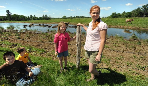 "Jessica Farrar with her children (from left) Aidan, 10, Aniston, 5, and Aislinn, 7, at their Appleton water buffalo farm. Jessica and her husband Brian started the farm in 2008 and now sell meat at farmer's markets, restaurants and stores in the midcoast area.  ""We would like to raise the number of the animals to about 30 so we can continue selling meat and start milking them as well,"" Jessica Farrar said."