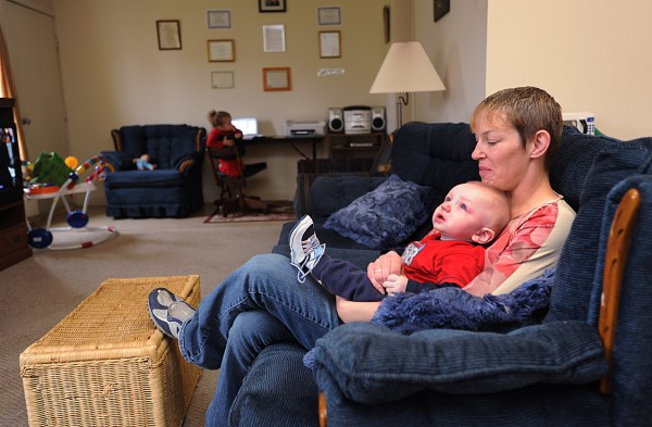 "Anne Buzzell sits at her home off Griffin Road with her children Jacob, 6 months old, and her daughter Vivian, 2 years old on Saturday, June 26, 2011, as she recounts the days that led up to her husband, Christopher M. Buzzell's problems with the use of ""bath salts."""