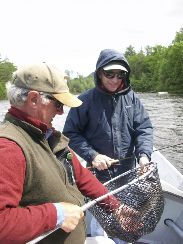 Dan Legere of Maine Guide Fly Shop (left) holds the net and a landlocked salmon that Don Factor of Bangor (right) caught Sunday on the West Branch of the Penobscot River. Factor was this year's winner of the BDN's annual &quotWin a Drift Boat Trip&quot contest.