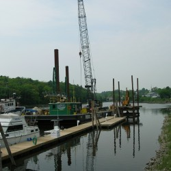 A crew from Prock Marine in Rockland prepares to set pilings into ledge on the Union River in Ellsworth this week. The pilings will support the new dock and slip system at the Ellsworth harbor marina. Prock Marine was called in partway through the project after the contractor hit the ledge.