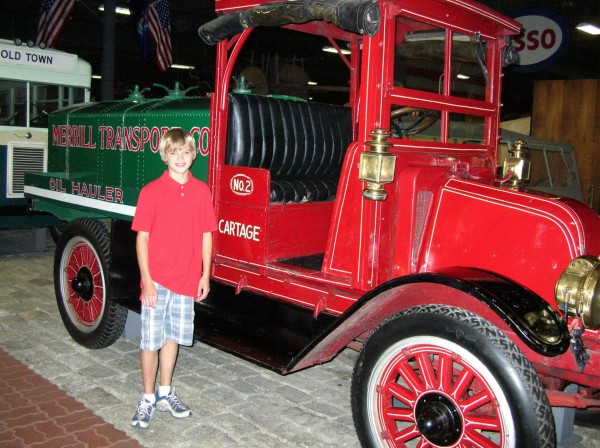 Ethan Merrill, grandson of Paul E. Merrill, stands by the 1920 Model H truck representing Merrill Transport at Cole Land Transportation Museum in Bangor. Ethan's mother recently donated the truck to the museum.
