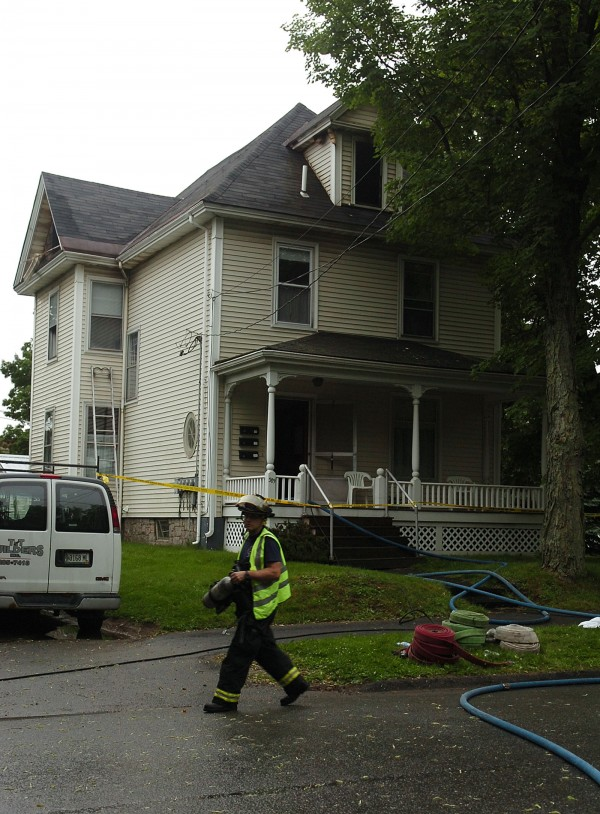 Bangor firefighters clean up at around 8 a.m. after extinguishing a fire at 389 Center Street in Bangor on Saturday, June 25, 2011. The flames broke out in the multi-unit building in the early morning hours.