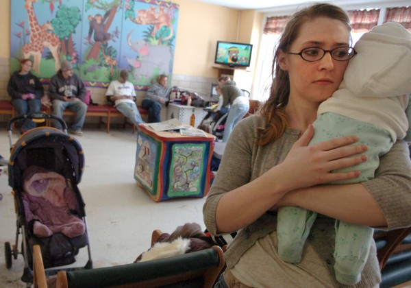 Francesca, who declined to give her last name, holds her 3-month-old daughter, Una, as they wait to meet with a social worker at Bangor's Health and Community Services office recently. Francesca, a 24-year-old single mother of two, has been receiving general assistance, which is a temporary subsidy given by Maine municipalities to help cover housing, heat and basic living expenses for a short period of time. Francesca hasn't been able to secure employment and is thinking about going back to school to study psychology.