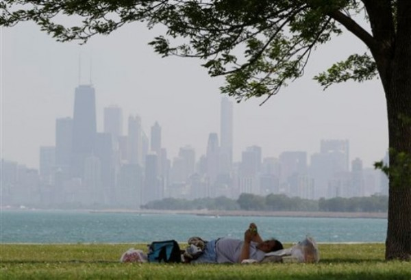 A woman rests during hot weather at Montrose beach in Chicago, Wednesday, June 8, 2011. Temperatures peak within a few degrees of the 97-degree 1933 record. Hottest early season spell in 34 years to break amid powerful, potentially severe storms Wednesday evening and night.