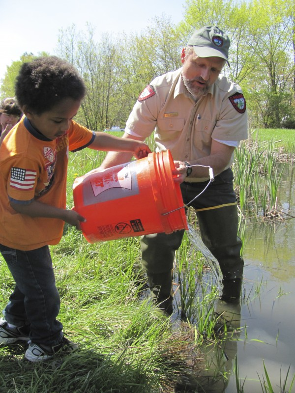 5-year-old Ari Abruzzese of Canaan releases two brook trout into Hight Pond near downtown Skowhegan on Friday, May 13, 2011. Assisting Abruzzese is Gene Arsenault, a fish culture supervisor for the Maine Department of Inland Fisheries and Wildlife's Embden hatchery.