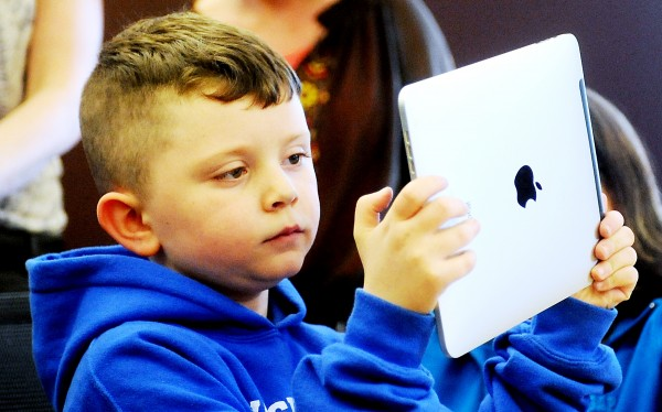 Lucius Rice, 6, uses an iPad during press conference where he distributed new iPads to five kindergarten teachers Tuesday. He also demonstrated apps he can use to help with learning.