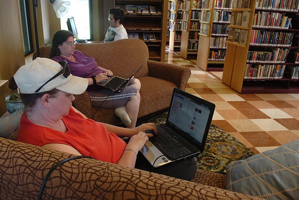 Rebecca Wilson (left) of Old Town, Shannon Buck (center) of Greenbush, and Charles Rogan (right, in background) of Orono, access the internet at the Old Town Public Library in Old Town on Wednesday, June 22, 2011. Wilson says that she comes to the library almost every day to use the free wireless internet, while her 12-year-old son often joins her and checks out books. According to library director Cynthia Jennings, in recent years the library has undergone a transition, attracting new patrons through innovative programming and by &quotcreating spaces so people come and stay.&quot  Jennings said that in addition to increased educational and entertainment programs, comfortable inside spaces and relaxing outside gardens have helped make the Old Town library a desirable meeting place for homeschooling groups, business training seminars, quilting groups, independent book groups and community forums. Jennings stated, &quotOne of our goals is to become a destination instead of a transaction library.&quot