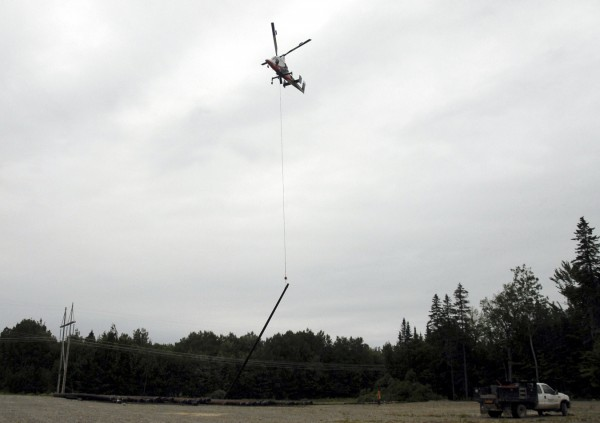 A Kaman K-MAX helicopter flew 150 utility poles from a lot off River Road in Chester to a site where a 115-kilovolt electrical line is being installed on Friday, June 24, 2011.