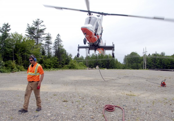 Flight engineer Shawn Clarke of British Columbia walks away from the climbing Kaman K-MAX helicopter after a brief refueling stop on Friday, June 24, 2011. The Connecticut-built medium-lift helicopter flew 150 utility poles from a lot off River Road in Chester to a site where a 115-kilovolt electrical line is being installed.