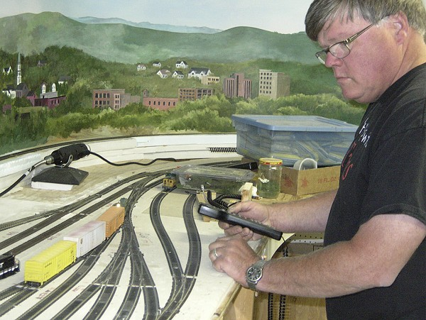 Geoff Anthony uses a hand-held controller to run a model train around the tracks on the layout at the Eastern Maine Model Railroad Club in Orland. Club work on the layout during regular club meetings.