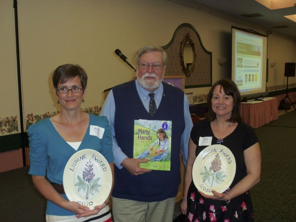 """Many Hands, A Penobscot Indian Story,"" written by Hampden resident Angeli Perrow (right) and illustrated by Heather Austin (left), formerly of Orrington, was chosen unanimously as the 2010 Lupine Award Winner in the picture book category. The award was presented by the Maine Library Association in a ceremony on April 14 at the Augusta Civic Center. Established in 1998, the Lupine Award honors a Maine author and-or illustrator who has created a work of outstanding merit for young people. Holding the book is Terry Bregy of Down East Books, publisher."