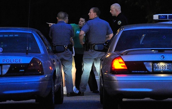 State Police and Bangor Police talk to on-site staff in a parking lot at Dorothea Dix Psychiatric Center after a suspect in the recent Fourth Street slaying in Bangor went missing there Tuesday evening, June 28, 2011.
