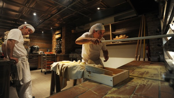 Massimo Ranni (right) uses a paddle to load his oven with bread as apprentice baker Brian Johnson (left) watches on Thursday, May 26, 2011 at Massimo's Breads on Hammond Street in Bangor. Massimo's Breads is Bangor's first European-style bakery.