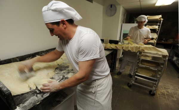 Massimo Ranni (left) makes casareccio from dough as apprentice baker Brian Johnson (left) puts the loaves on a tray for transport to the oven on Thursday, May 26, 20111 at Massimo's Breads on Hammond Street in Bangor. Massimo's Breads is Bangor's first European-style bakery.