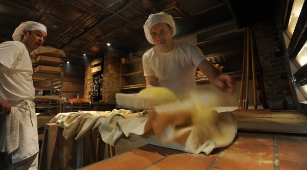 With the flip of his wrist, Massimo Ranni (right) pops a roll of dough on to a tray before putting it into the oven at Massimo's Breads in Bangor on Thursday, May 26, 2011 as apprentice baker Brian Johnson (left) watches and learns.