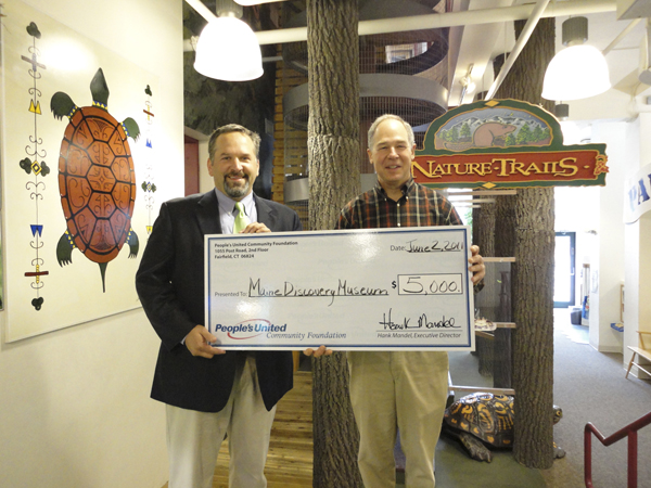 Bill Lucy, Officer People's United Community Foundation and division President, People's United Bank (right) presents Niles Parker, Executive Director Maine Discovery Museum, a check for $5,000.