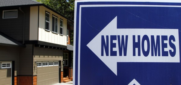A sign points the way to new homes for sale in Happy Valley, Ore., last month. An index of home prices in big metro areas has reached its lowest level since 2002, driven down by foreclosures, a glut of unsold homes and the reluctance or inability of many to buy.
