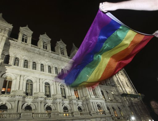 Robert Moore of New York waves a pride flag outside the Capitol in Albany, N.Y., after the state Senate passed a bill legalizing same-sex marriage on Friday, June 24, 2011.