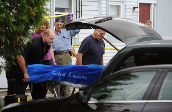Bangor police and Maine State Medical Examiner's Office personnel remove the body of a man from an apartment at Ledgewood I apartments complex on Ohio Street in Bangor on Monday, June 13, 2011.