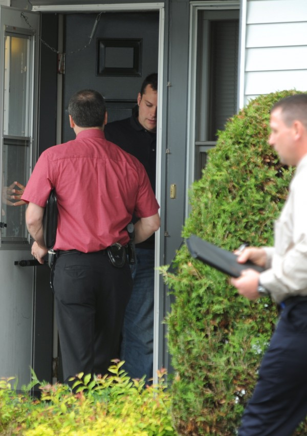 Detectives with the Bangor police go door to door as they investigate the death of a man at apartment 24 in the Ledgewood 1 apartment complex on Ohio Street on Monday, June 13, 2011.