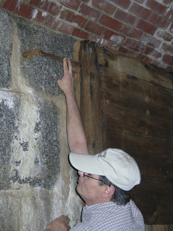 "Leon Seymour, executive director of the Friends of Fort Knox fits an iron ""dog"" into holes in the granite walls in the powder magazine at the Fort Knox Historic Site in Prospect. The ""dog"" was uncovered by crews working on a restoration project in the magazine, an area that has been closed to the public for safety reasons for at least 50 years."