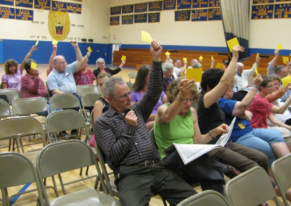 RSU 20 residents signify their approval for a budget article they voted on Thursday night at the Belfast Area High School gymnasium. It took voters just under two hours to approve the next fiscal year's $32.7 million budget.