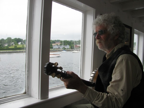 Musician Wes Cotton of Unity played some tunes on his banjo Thursday morning as the 19th century replica steam ferry Patience chugged out of Belfast Harbor.