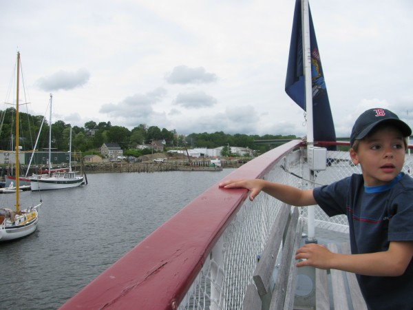 Colby Terry, 8, of Prospect, stands at the bow of the steam ferry replica Patience as his aunt, Captain Melissa Welch, prepares to dock the 72-foot long boat at Thompson's Wharf in Belfast.
