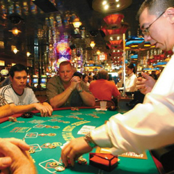 Dealer Patrick Chen collects chips on the poker table as players look on at an Atlantic City casino. The Maine House on Wednesday approved a measure to allow Hollywood Slots in Bangor to offer table games such as poker, craps and roulette.