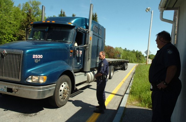 Maine State Trooper Josh D'Angelo, left, and Trooper Philip Pushard, right, watch as a commercial vehicle pulls in for a mandatory inspection at an I-95 stop in Old Town on Tuesday, June 7, 2011. The inspection was part of a three-day safety and security check conducted by the Maine State Police's Commercial Vehicle Enforcement Unit as part of Roadcheck 2011, an annual event which takes place throughout the United States, Canada, and Mexico. All commercial vehicles and their operators traveling on I-95 were required to submit to inspection, with stops also being conducted in Kittery, York, Sidney, Pittsfield, and Houlton. Additionally, roving patrols were inspecting vehicles traveling other Maine roads.