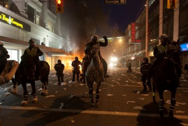 Police on horseback move down a street during a riot following the Vancouver Canucks being defeated by the Boston Bruins in the NHL Stanley Cup Final in Vancouver, British Columbia, Wednesday.