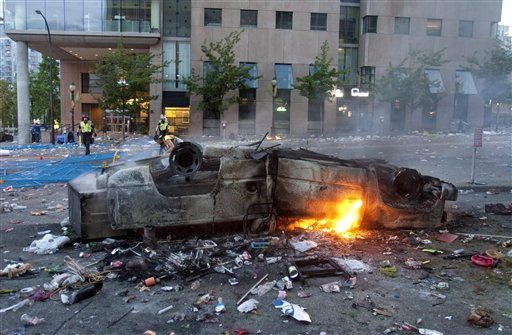 A burnt out car lies upside down in the street following the Vancouver Canucks being defeated by the Boston Bruins in the NHL Stanley Cup Final in Vancouver, British Columbia, Wednesday.