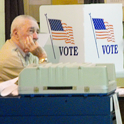 An worker mans his post during an election in Houlton in 2010. The Maine House on Monday gave its preliminary approval to bills that would end same-day registration and require voters to provide photo identification at the polls.