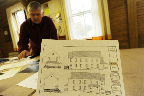 Jim Smythe, chairman of the Willimantic building committee, shows an architectural rendering of the Willimantic Town Hall meeting room recently. Use of the facility after recent renovations has been restricted to the first floor due to code violations discovered during construction. Residents' concerns about structural problems left behind by the renovation of the Town Hall were validated Thursday, June 2, by a structural engineer retained by the town. Town officials have spent about $93,500 to renovate the hall, but those renovations were done without an engineering plan or a permit from the State Fire Marshal's Office.