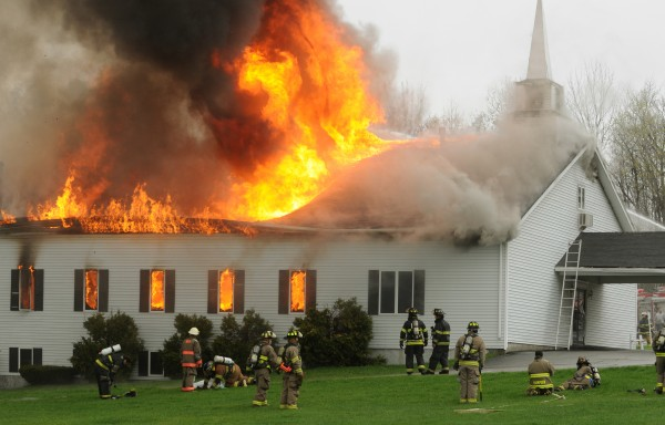 Firefighters from numerous departments pull back as the roof collapses on the Calvary Apostolic Church in Winterport last month. The church says it will be used again and is in the beginning stages of making rebuilding plans. Rev. Tom Channell of the church says they are planning on building a family life center.