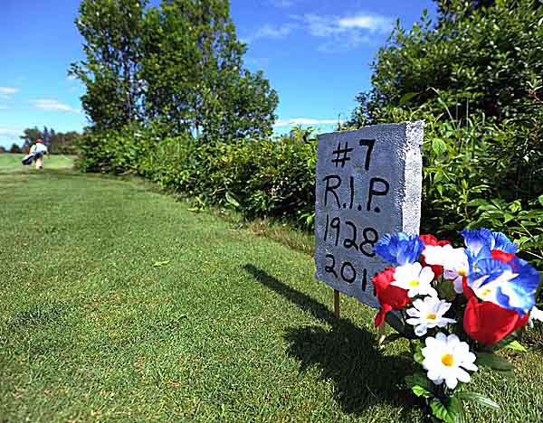 A headstone and plastic flowers mark the former No. 7 tee box at Island County Club  on Deer Isle on Friday, July 7, 2011.